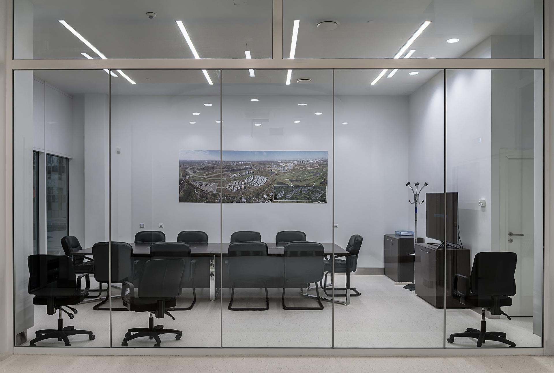 Biuro ze ścianami szklanymi. W środku kilka foteli i stół.