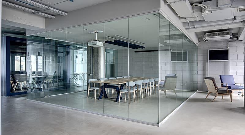 Wydzielone szklanymi ścianami biuro.